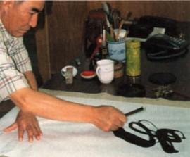 Каллиграф наносит иероглифы на рисовую бумагу